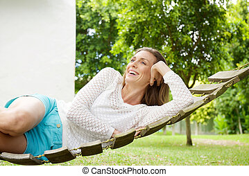 Beautiful woman smiling on hammock outdoors