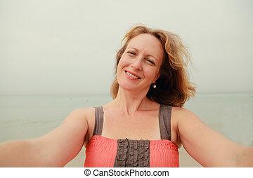 Beautiful woman smiling on the beach. Selfie.
