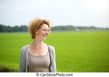 Beautiful woman smiling outdoors by green countryside