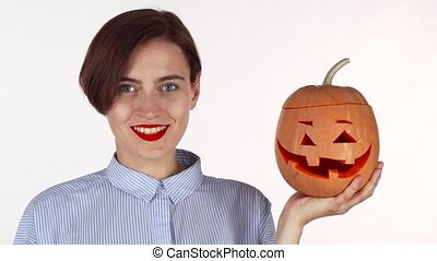 Beautiful woman smiling to the camera, holding halloween carved pumpkin