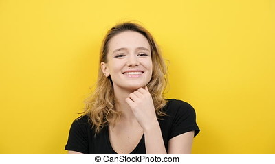 Beautiful woman smiling to the camera on yellow background
