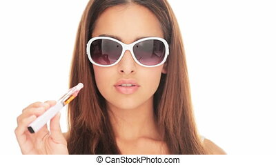 Beautiful woman smoking an e-cigarette which is a...