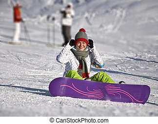 Beautiful woman snowboarder sitting on the ski slope....