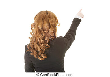 Beautiful woman standing and pointing up, back view.