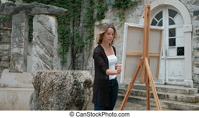 Beautiful woman standing at an easel and holding a brush and palette.