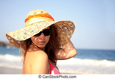 beautiful woman standing by the sea in a  hat