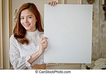 Beautiful woman standing, holding white blank advertising.