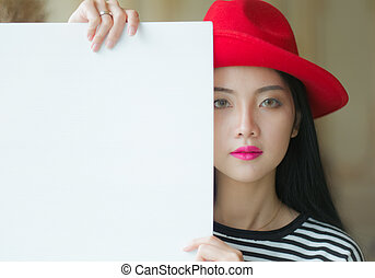 Beautiful woman standing, holding white blank advertising board