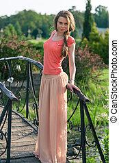 Beautiful woman standing in a park near the bridge