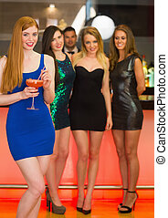 Beautiful woman standing in front of her friends holding...
