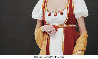 Beautiful woman standing in old historical 18th century royal dress on black background in studio. Look of Marie Antoinette on ball. Details of costume, treasure jewelry.