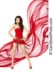 Beautiful woman standing in red flying dress. Hands on hips. Chiffon flutter on a wind flow over white background