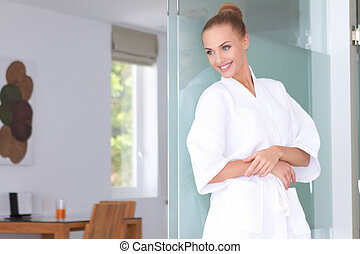 Beautiful woman standing in white bathrobe