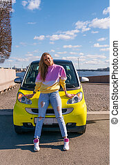 beautiful woman standing near a yellow car on a Sunny day