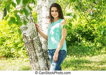 Beautiful woman standing near tree in summer park