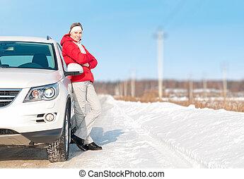 Beautiful woman standing near white car in winter.