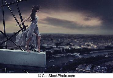 Beautiful woman standing on a cornice