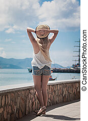 Beautiful woman standing on city embankment and enjoying the view, In a straw hat, with his back to the camera