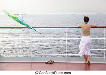 beautiful woman standing on deck of cruise ship and looking away.