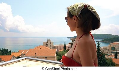 Beautiful woman standing on the seaview terrace on a summer day