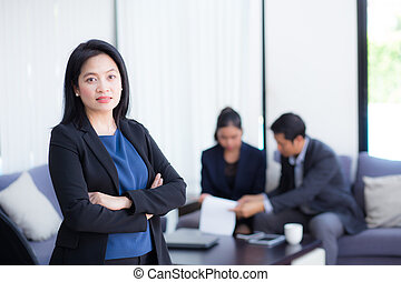 Beautiful woman standing with arms folded with colleagues in team on background