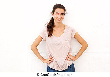 Beautiful woman standing with hands on hips against white background