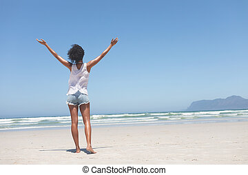 Beautiful woman standing with open arm at beach on sunny day