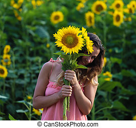 beautiful woman stands in a field of sunflowers - Young...