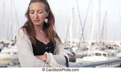 Beautiful woman stands in on the pier at the yacht parking