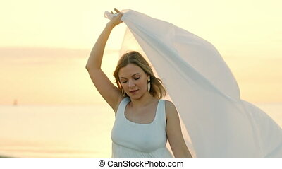Beautiful woman stands on sea beach and holds long white fabric veil, like sails fluttering in wind. Concept of femininity, tenderness, freedom. High quality 4k footage