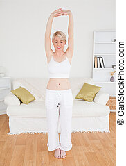 Beautiful woman stretching in the living room