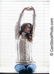 Beautiful woman stretching sitting on window sill