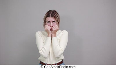 Beautiful and funny young caucasian woman wearing white sweater over isolated gray background suffering pain on hands and fingers, arthritis inflammation, looking scary