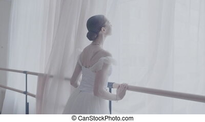Beautiful woman takes a breath before an open window
