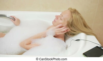 beautiful woman taking a bath and listening to music on headphones. cell phone