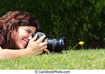 Profile of a beautiful woman taking a macro photography of a flower on the grass in a park
