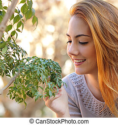 Beautiful woman taking care of a little tree