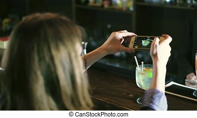 Beautiful woman taking pictures of a cocktail at the bar 4k