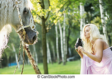 Beautiful woman taking pictures of the horse