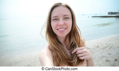 beautiful woman taking selfie using phone on beach at sunset smiling
