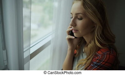 Beautiful woman talking on phone at home