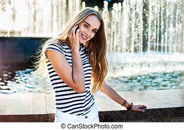 Beautiful woman talking on phone in the city near the fountain