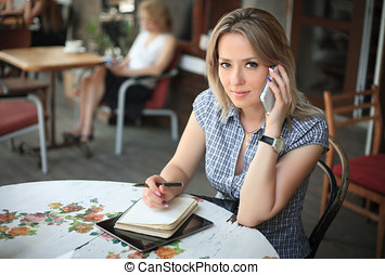 Beautiful woman talking on the phone in a cafe.