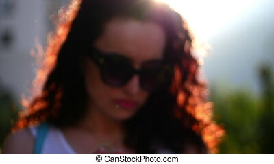 Beautiful woman talking on the phone outdoors. A young mother is talking on the street. A woman with glasses. Slow motion.