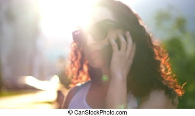 Beautiful woman talking on the phone outdoors. She smiles, and the bright rays of the sun against the backdrop of the city can be seen in the background behind her.