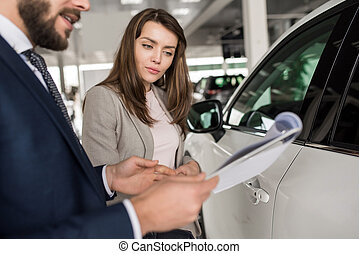 Beautiful Woman Talking to Car Salesman