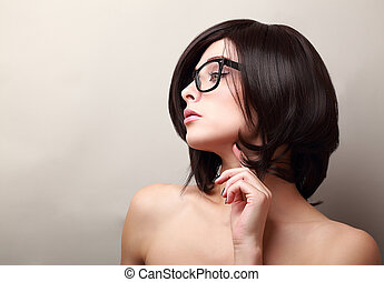 Beautiful woman thinking in glasses. Closeup portrait with empty space