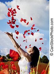 woman - beautiful woman throwing red poppy petals in the air