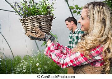 Beautiful woman touching a hanging flower basket in a green...