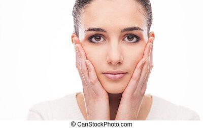 Beautiful woman touching her face